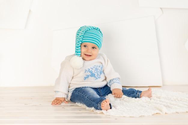 Een klein gelukkig kind van zes maanden oud in een gebreid warm jasje en een pet zit thuis op een kleed in een lichte kamer