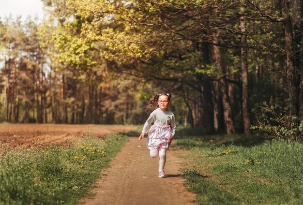 Een klein gelukkig meisje rent in de zomer op een zonnige dag langs een bospad