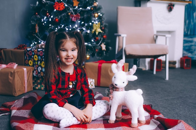 Een klein gelukkig meisje van vijf jaar oud zit bij de kerstboom met geschenken met haar favoriete speelgoed, een hert kijkt in het frame en glimlacht.
