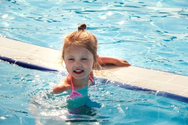 Een klein gelukkig meisje zwemt in de zomer op vakantie in de middag in het zwembad en geniet van de zon