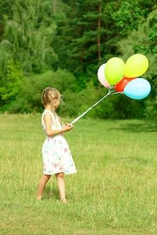 Een klein gelukkig meisjeskind met ballons op aard