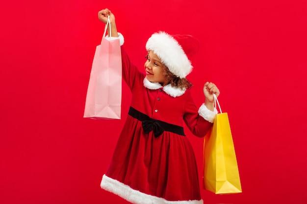 Een klein gelukkig zwart meisje met een kerstmuts en een draagtas maakt cadeautjes klaar voor kerstmis