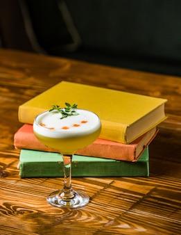 Een klein glas vanille melk cocktail op een houten tafel met boeken rond.