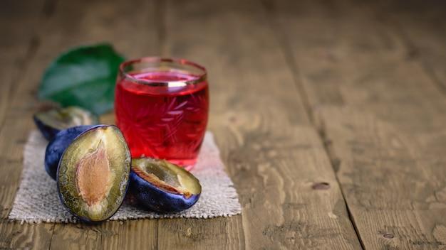 Een klein glas zelfgemaakte alcohol van bessenpruimen op een houten tafel.