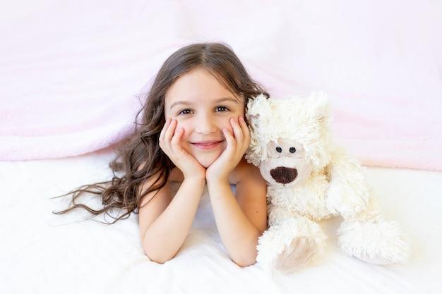 Een klein glimlachend meisje van 5-6 jaar oud ligt in bed met een teddybeer
