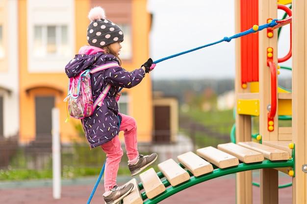 Een klein grappig meisje in een warme jas, hoed en grappige rugzak klimt een houten glijbaan met behulp van een touw in een speeltuin in een stadspark.