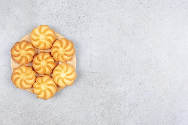 Een klein houten dienblad met koekjes op marmeren achtergrond.