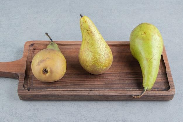 Een klein houten dienblad met peren op marmer