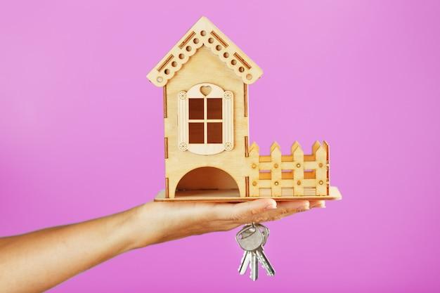 Een klein houten huis met sleutels in hand op een roze achtergrond.