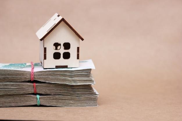 Een klein houten huis op de bundels van 1000 duizendste russische roebelbiljetten. het idee om een woning te kopen. een grote aankoop