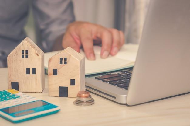 Een klein houten huis op het bureau een man laptopcomputer en rekenmachine