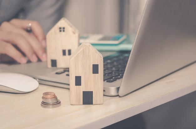 Een klein houten huis op het bureau een man met een pen en een laptopcomputer en rekenmachine