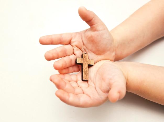 Een klein houten kruis in de handen van het kind