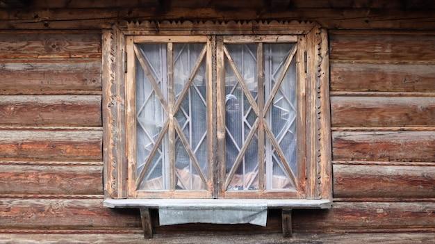 Een klein houten raam van een traditioneel oud huis. het raam is gesloten en bruin. een oud raam met een houten frame van planken, dat deel uitmaakt van een oud rustiek houten huis op een zonnige zomerdag.