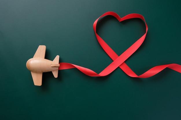 Een klein houten speelgoedvliegtuig draagt valentijnsdagelementen. dampspoor in de vorm van een hart, en rood lint in de vorm van een hart. valentijnsdag