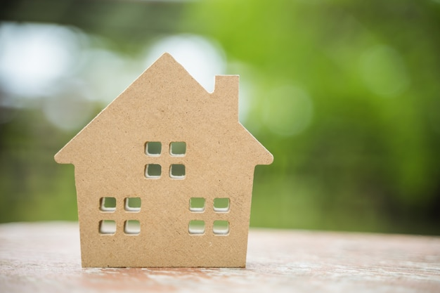 Een klein houten stuk speelgoed huis met vage achtergrond