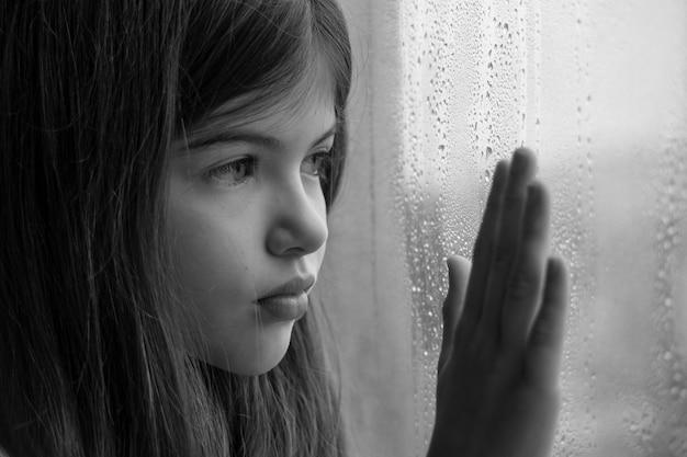 Een klein jong meisje zit bij het raam en is triest kinderproblemen eenzaamheid concept zwart-wit foto
