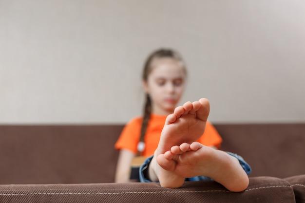 Een klein kaukasisch meisje dat met naakte voeten boek leest terwijl thuis het zitten op een bank. voet close-up. selectieve aandacht