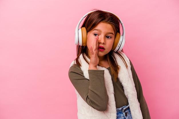 Een klein kaukasisch meisje dat muziek luistert die op een roze achtergrond is geïsoleerd, zegt een geheim heet remnieuws en kijkt opzij