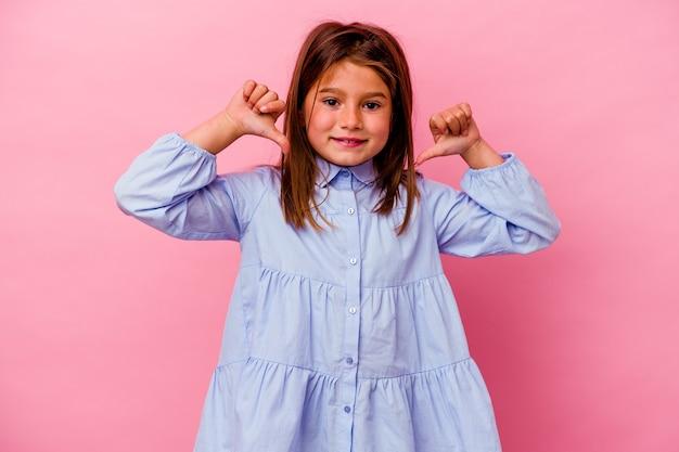 Een klein kaukasisch meisje geïsoleerd op een roze achtergrond voelt zich trots en zelfverzekerd, een voorbeeld om te volgen.
