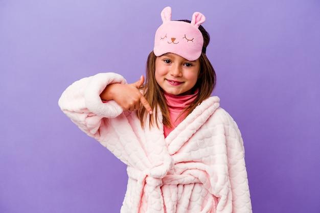 Een klein kaukasisch meisje met een pyjama geïsoleerd op een paarse achtergrondpersoon die met de hand wijst naar een ruimte voor een shirtkopie, trots en zelfverzekerd