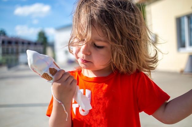 Een klein kaukasisch meisje met een smeltend ijsje dat op haar hand stroomt. warme zomerdag