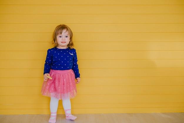Een klein kaukasisch meisje poseert voor een kindertijdschrift over gele muur