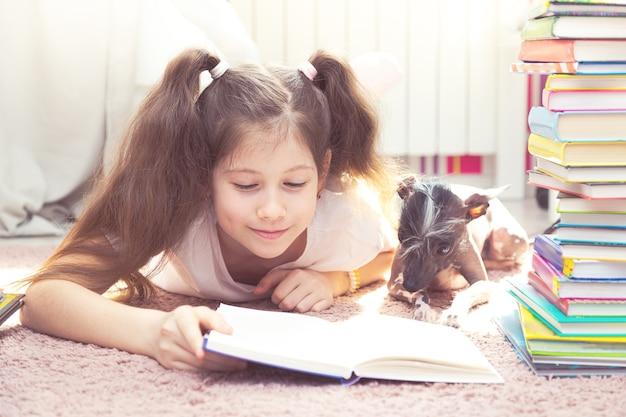 Een klein kaukasisch meisje speelt met een hond op de vloer. er zijn veel boeken om hen heen. het meisje probeert te lezen, de hond bemoeit zich met haar.