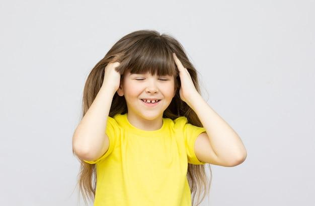 Een klein kaukasisch meisje zit en raakt haar haar aan op een witte achtergrond