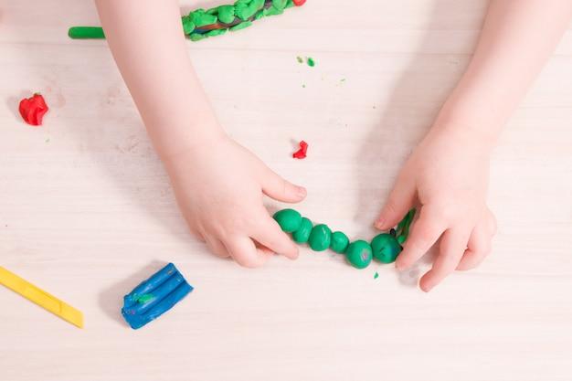 Een klein kind beeldhouwt een rups uit groene plasticine op een houten tafel