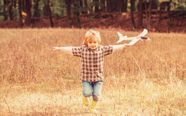 Een klein kind droomt ervan piloot te worden. gelukkig jongen speel vliegtuig. kleine jongen met vliegtuig. kind spelen met speelgoed vliegtuig.