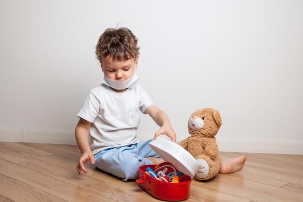 Een klein kind, een jongen met een medisch masker met een stethoscoop om zijn nek, speelt een dokter met een medicijnkastje voor kinderen, geeft een teddybeer een injectie en meet de temperatuur