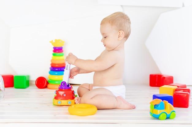 Een klein kind, een jongen van zes maanden oud, speelt met helder speelgoed in een helderwitte kamer in luiers