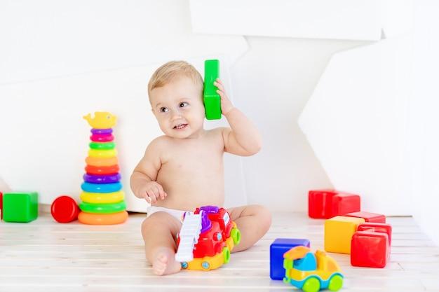 Een klein kind, een jongen van zes maanden oud, speelt met heldere blokjes in een helderwitte kamer in luiers alsof ze aan de telefoon zitten
