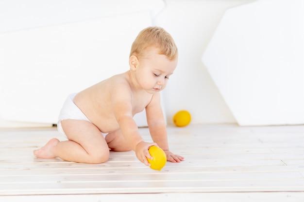 Een klein kind, een jongen van zes maanden oud, speelt op de vloer in een helderwitte kamer in luiers met citroenen en sinaasappels