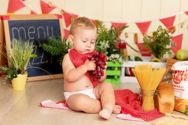 Een klein kind, een jongen van zes maanden oud, zit op de keukenvloer met druiven