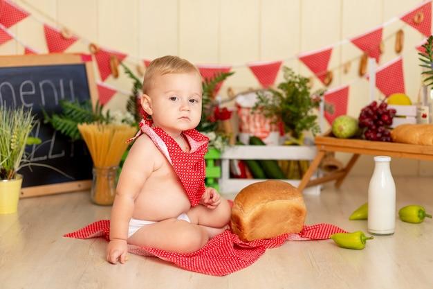 Een klein kind, een jongen van zes maanden oud, zit op de keukenvloer met een brood
