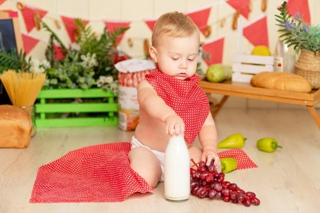 Een klein kind, een jongen van zes maanden oud, zit op de keukenvloer met een fles melk en druiven