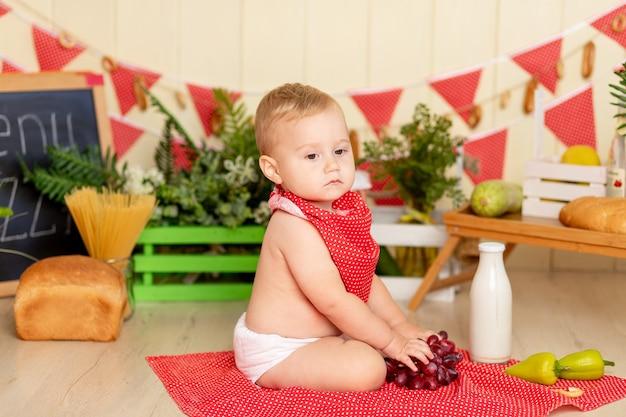 Een klein kind een jongen zit op de keukenvloer met een fles melk en druiven