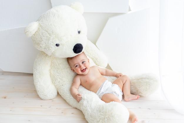 Een klein kind, een meisje van 6 maanden oud, ligt op een grote zachte beer in een licht appartement in luiers