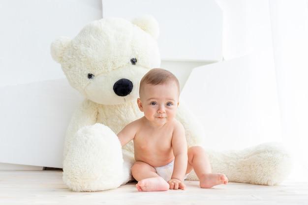 Een klein kind, een meisje van 6 maanden, zit met een grote zachte beer in een licht appartement in luiers