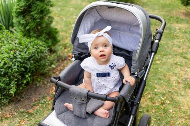 Een klein kind een meisje van 7 maanden zit in de wandelwagen in de zomer in een witte jurk en kijkt naar de camera