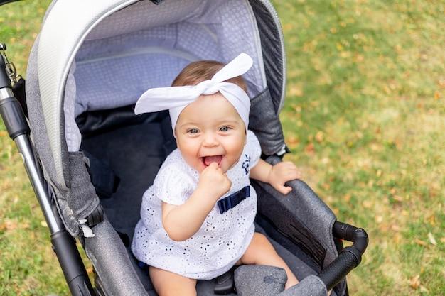 Een klein kind een meisje van 7 maanden zit in de wandelwagen in de zomer in een witte jurk en lacht