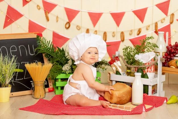 Een klein kind, een meisje van zes maanden oud, zit in de keuken in de kleren van een kok met een brood