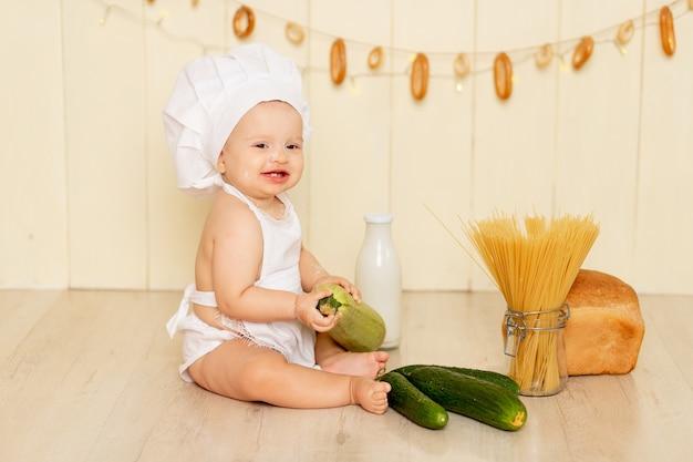 Een klein kind, een meisje van zes maanden oud, zit in de keuken in een koksmuts en een schort en eet een groene pompoen