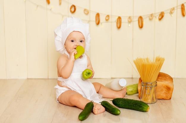 Een klein kind, een meisje van zes maanden oud, zit in de keuken met een koksmuts en een schort en eet groene paprika's