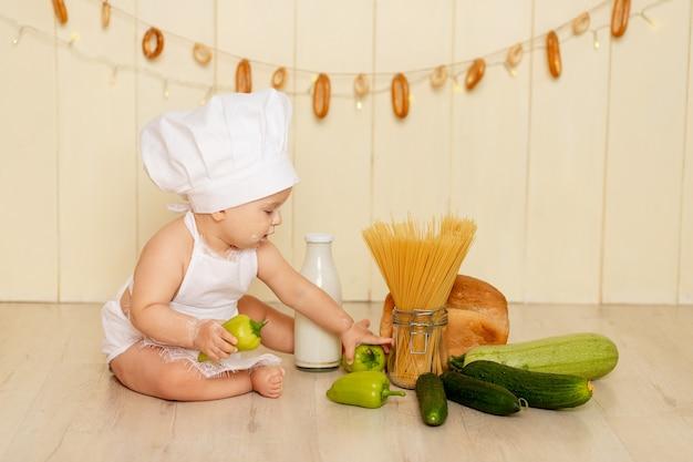 Een klein kind, een meisje van zes maanden oud, zit in de keuken met een koksmuts en een schort en houdt een groene paprika vast