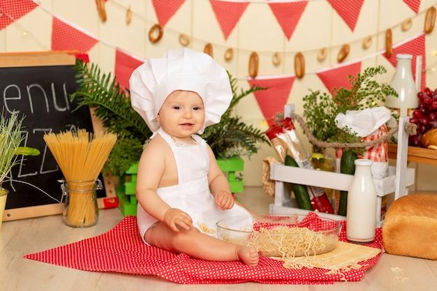 Een klein kind, een meisje van zes maanden oud, zit in de keuken verkleed als chef-kok met een groot bord spaghetti