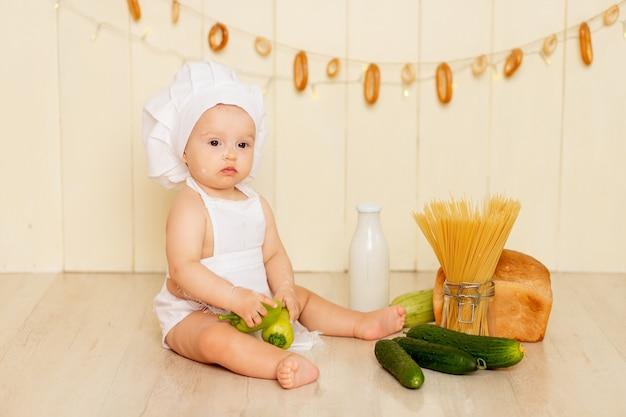 Een klein kind een meisje zit in de keuken met een koksmuts en een schort en houdt een groene paprika vast