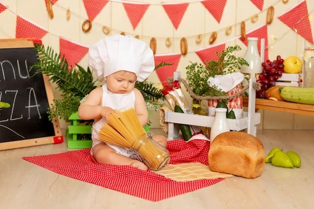 Een klein kind een meisje zit in de keuken verkleed als kok en speelt met spaghetti